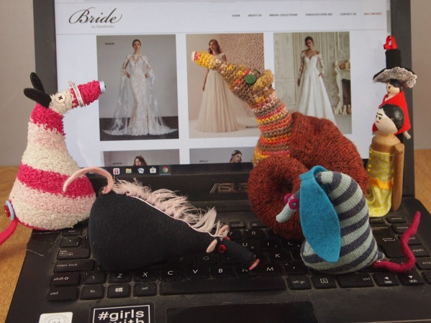 Esther and the others look at a dress with long lacy sleeves, while Fury lies on the keyboard