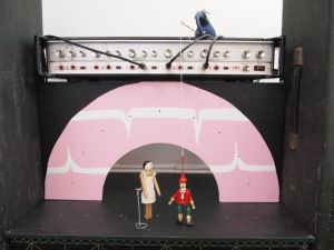 We see ernest on the stage roof dangling the puppet from a stick