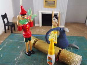 Gino has the motif stuck to the tip of his long nose. He and Peggy have their arms up in the air in surprise.