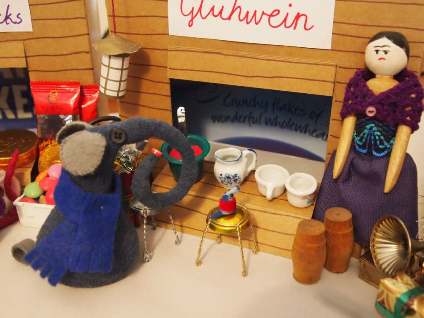 Ernest and Nano are at the Gluhwein stall, Nano is sitting on one of the bar stools
