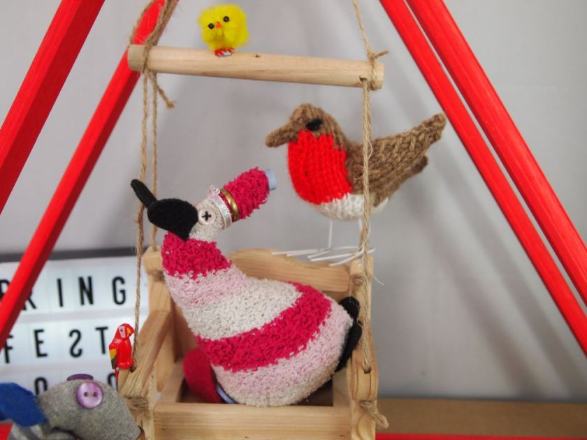 matilda is surprised by a large knitted robin appearing on the back of the swing