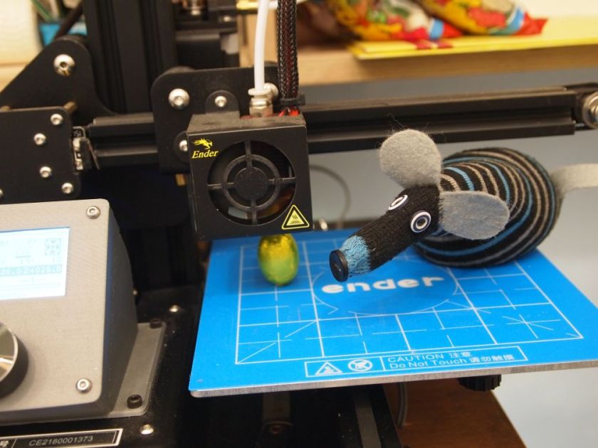 hypno sits on the bed of a 3D printer, looking at an egg formed under the nozzle