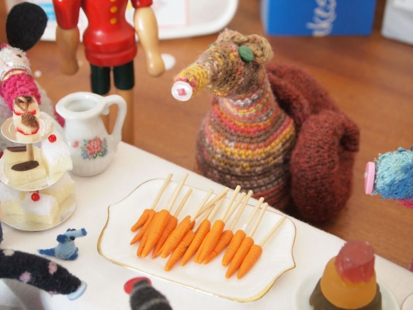 Esther brings a tray of carrots on sticks