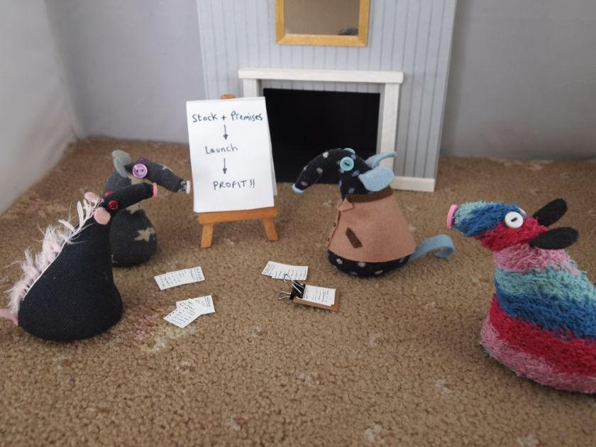 Ratvaark spots Winston Vincent and Fury having a meeting. They have papers, and a flip chart that says Stock plus Premises , Launch and Profit.