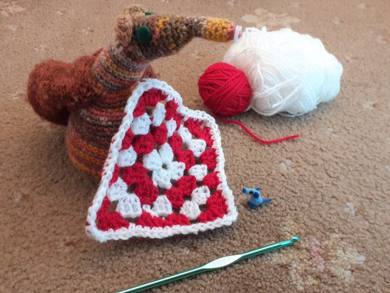 Esther shows Nano the finished square in red and white with a white edging