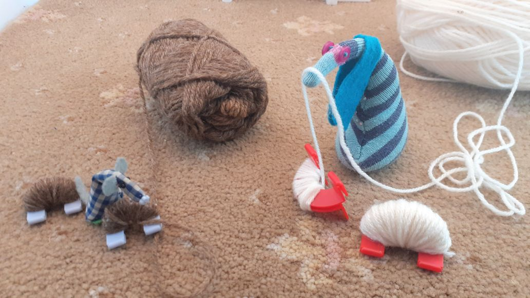 ofelia is winding white yarn round one maker, and micro is winding brown yarn round the other
