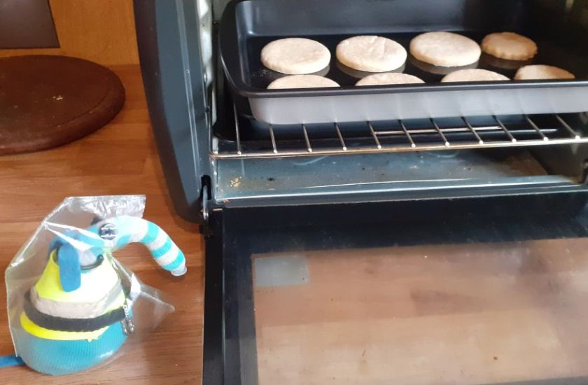 Arnold puts the biscuits in the oven