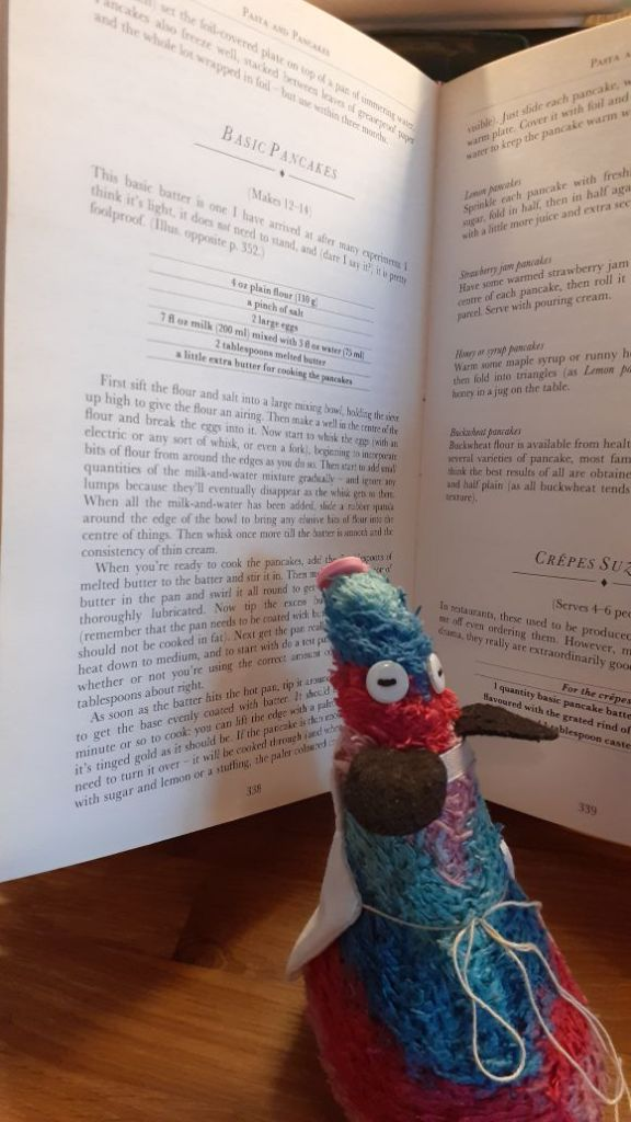 Ratvaark looks up a recipe for pancakes in a cookery book