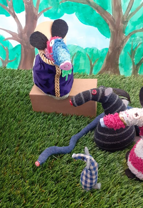 Microvaark looks at a long blue snake in the grass