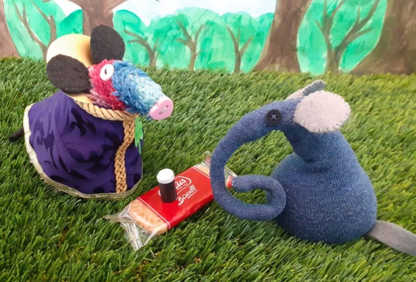 Ratvaark gives Ernest a biscuit and a glass of black with a white top on it.