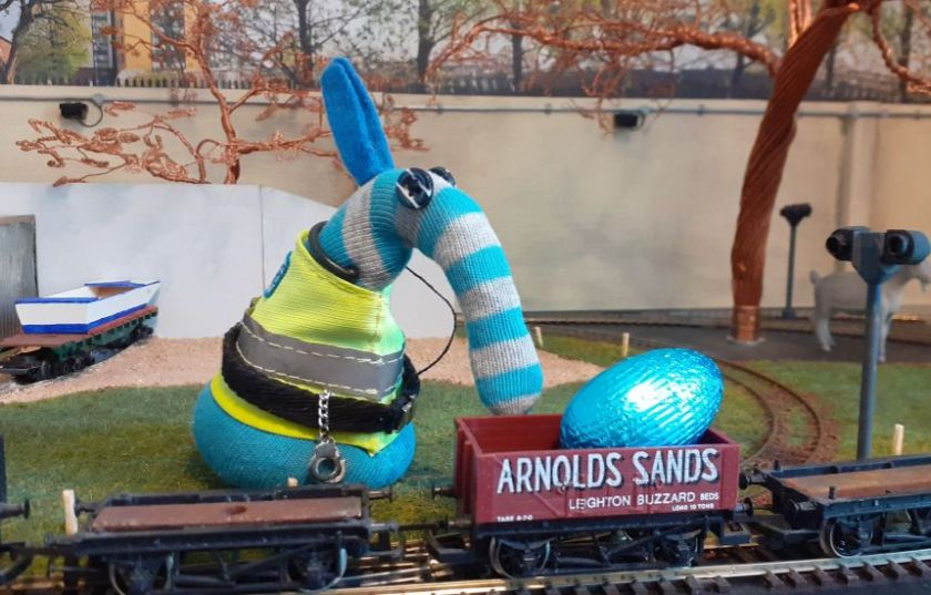 "Arnolds ears fly up in surprise as he looks at an egg sitting in a model railway truck with ""Arnolds Sands"" printed on the side."