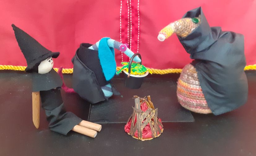 Esther, Peggy and Ofelia are gathered round a fire, and Ofelia carries a cauldron of green bubbling goo.