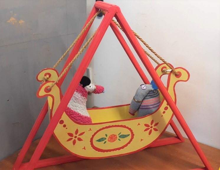 Dim and Matilda sit in a yellow swingboat with roses painted on it hanging from a red triangular frame.
