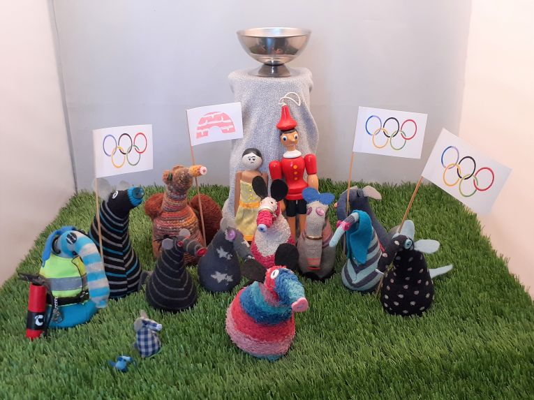 all the vaarks are gathered in front of a cauldron on top of a tall plinth, with Olympic flags