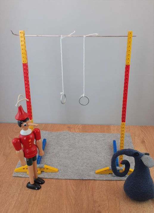 gino and ernest stand next to a set of gymnastic rings hanging from ropes