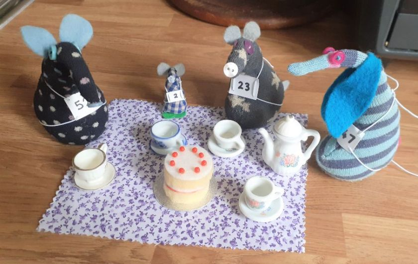 They sit around a cloth with teacups and a sponge cake
