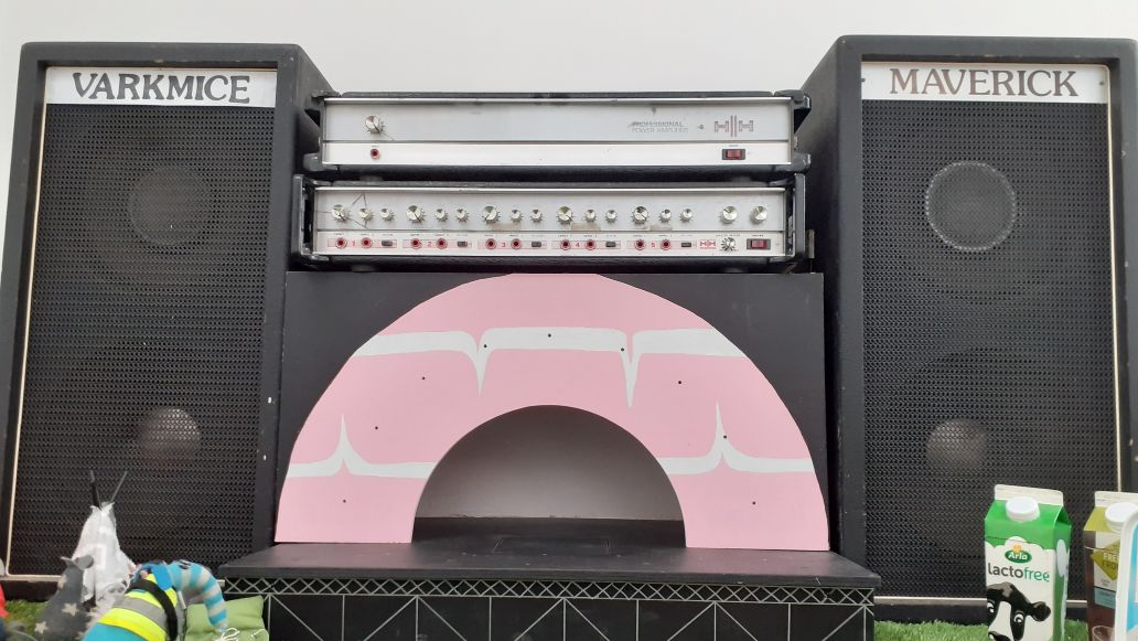 The stage has an arch painted like a Party Ring biscuit, with a huge speaker either side.
