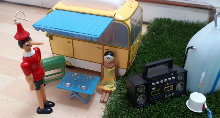 Peggy and Gino are standing beside a little yellow camper van with a barbecue and a table set up
