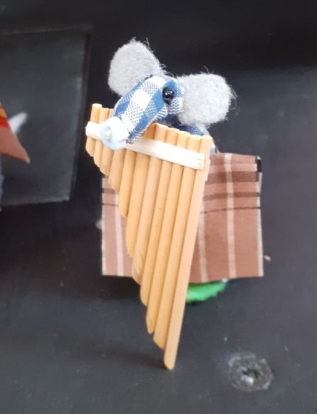 Micro plays the panpipes, the longest pipe is almost as tall as he his.