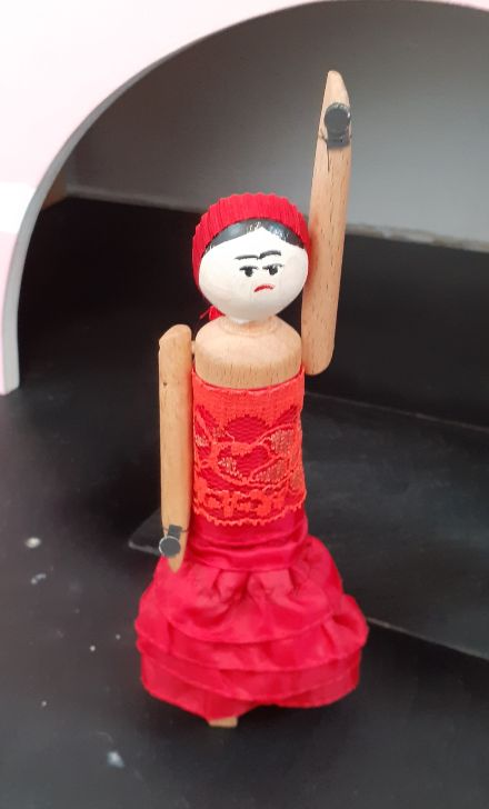 Peggy dances with one arm raised. She has castanets on her hands.