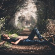 Man laying on pathway in plants and trees