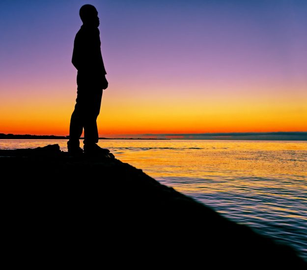 Man standing on cliff by water at sunset