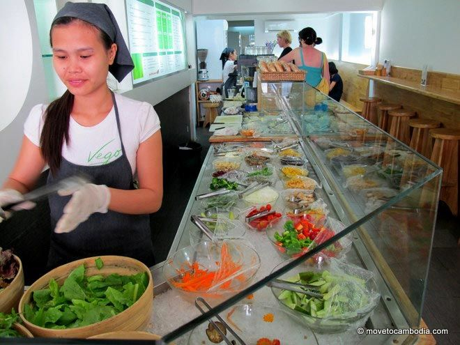 A woman working at a salad bar in Cambodia.