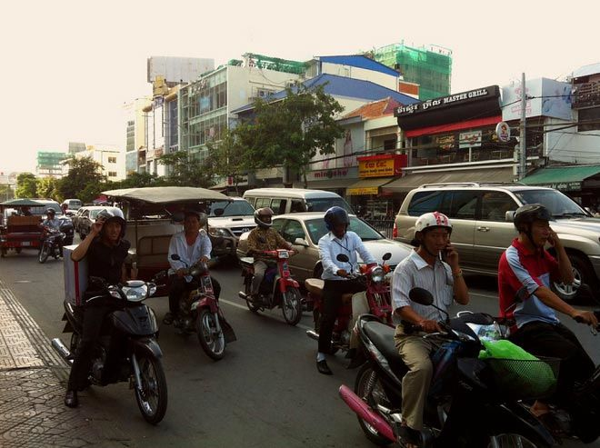 Phnom Penh traffic, including tuk tuks, SUVs and moto drivers busy driving and texting.