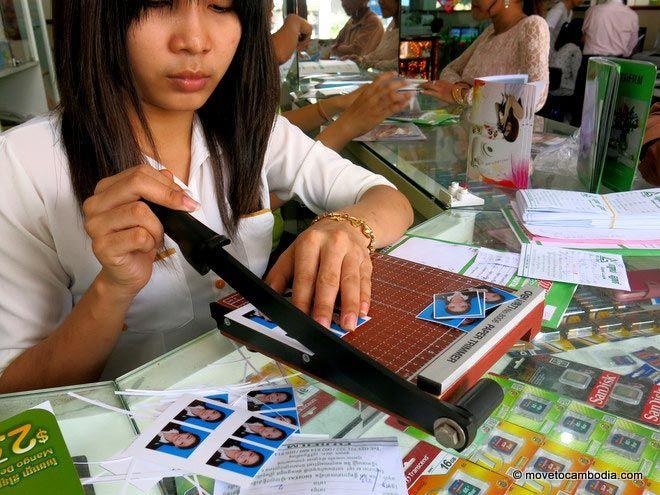 Girl cutting passport photos at Good Luck Printing Phnom Penh