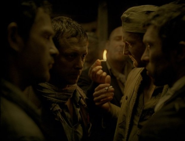 Prisoners huddle, smoking, in a scene in Son of Saul