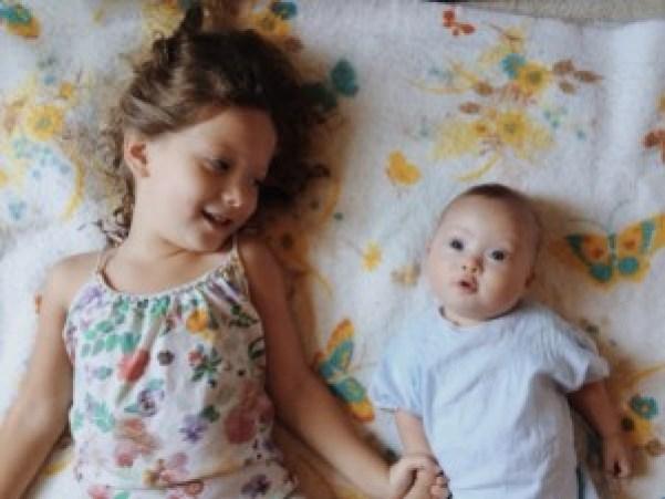 Pais escrevem música para filha com síndrome de Down. Na foto, a filha mais velha, que é uma criança e não tem síndrome de Down, e a filha mais nova, que é um bebê e tem síndrome de Down, aparecem deitadas. A filha mais velha olha com carinho para a mais nova e segura a sua mão.