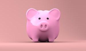A pink piggy bank on a pink surface.