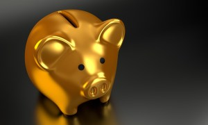 A gold piggy bank on a black surface.