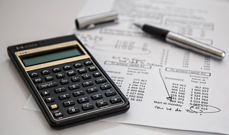 A calculator and a pen with some paper