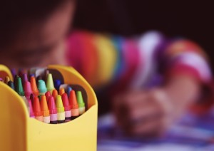 Close up of crayons and a girl behind them.