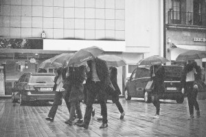 A group of people moving during a rainstorm.