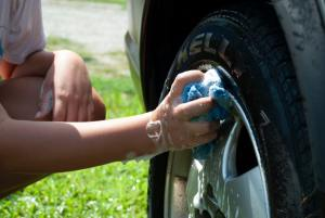 Person washing a tire to prepare vehicles for shipping.