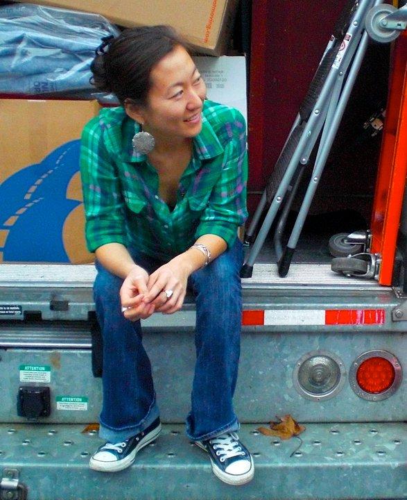 Mia Mingus sits on the back of the U-haul she took to California