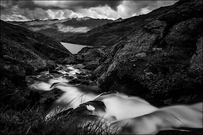 Une photo en noir et blanc d'un ruisseau dans les montagnes après la pluie.