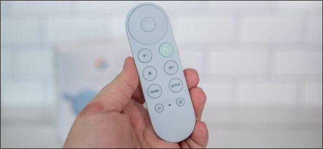 Jemand, der einen Chromecast mit der Google TV-Fernbedienung hält.