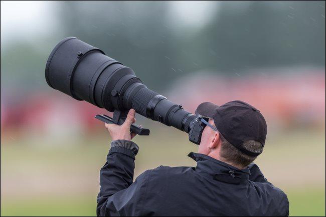 Un photographe utilisant un énorme téléobjectif.