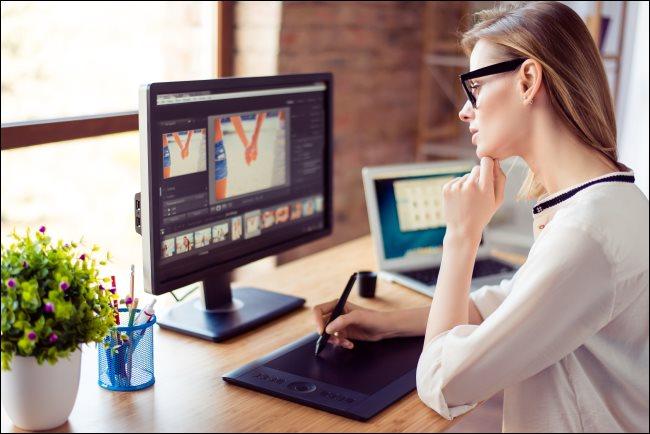 Une femme regardant un écran d'ordinateur tout en s'appuyant sur une tablette numérique.