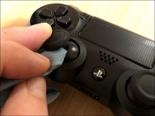 Une main nettoyant une clé analogique avec un chiffon sur un contrôleur DualShock 4.