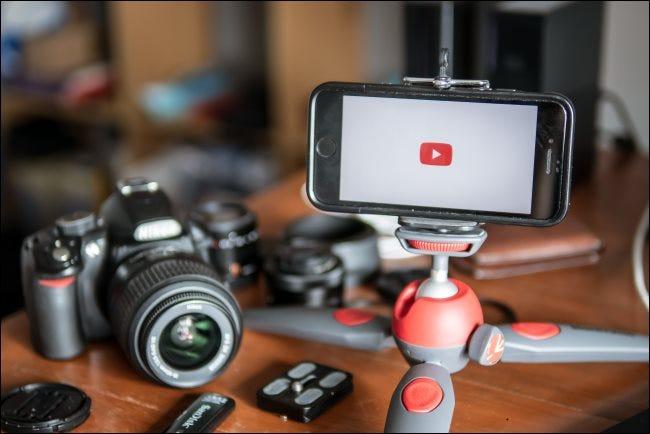 Eine Kamera, die auf einem Tisch neben einem auf einem Tischstativ montierten Smartphone liegt.