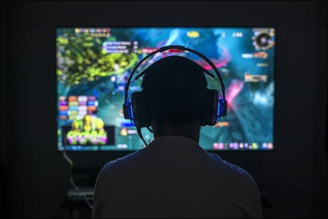 Ein junger Spieler, der ein PC-Spiel spielt, während er Kopfhörer trägt.