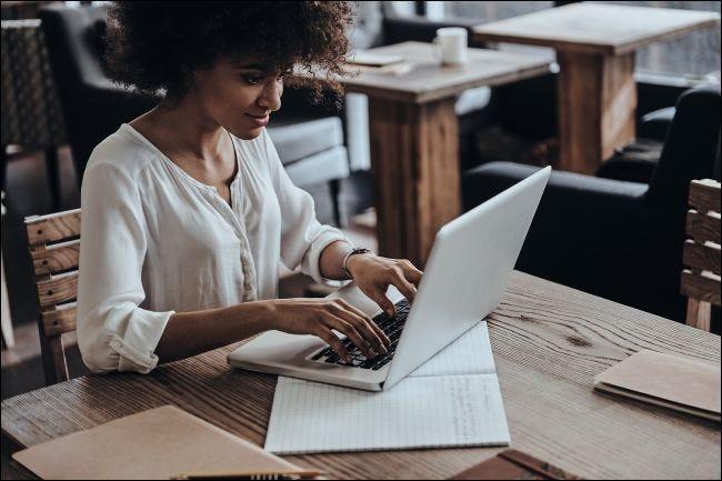 Una mujer sonriente escribiendo en una computadora portátil.