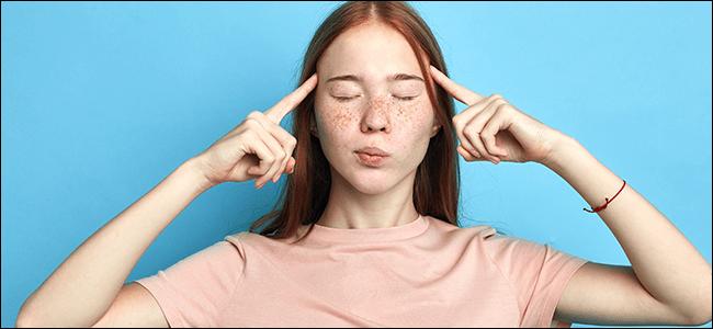 Ein Mädchen mit geschlossenen Augen hält ihre Zeigefinger an die Schläfen.