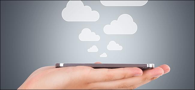 Une main tenant un téléphone alors que des nuages en sortent, symbolisant les fichiers enregistrés dans le cloud.