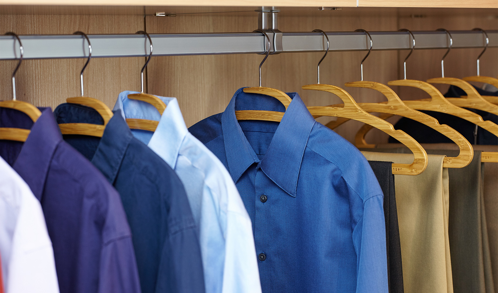 Multiple bamboo Mozu Hangers in closet with shirts and pants
