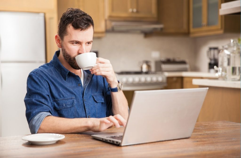 Man sitting at a table with his laptop having a drink